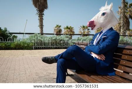 Unusual manager in elegant suit sits on the bench on the city street. Unicorn is enjoying warm weather outdoors