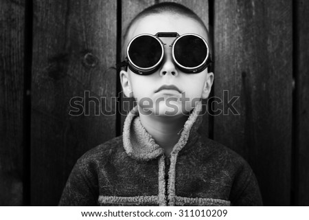 unusual portrait of a boy with welding glasses ,Old wooden background in behind,black and white photography