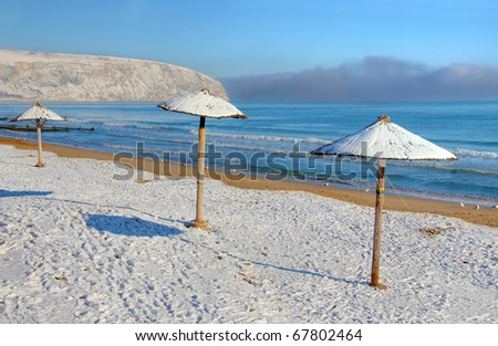 Unusual view of Hawaiian beach parasols covered in snow.