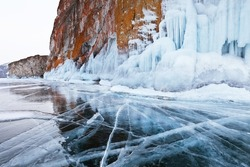Unusual winter landscape of frozen Baikal Lake with transparent blue ice with cracks near the icy cliffs of Olkhon Island on frosty February day. Natural background. Winter ice travel and activities