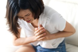 Unwell condition and sickness concept; Asian woman having heart attack sitting on sofa. She puts both hand on her left chest feeling painful and need emergency medical assistance.