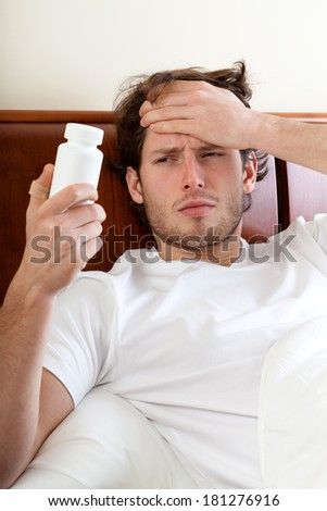 Unwell man with headache lying in bed