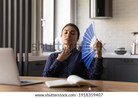 Unwell millennial Indian woman work on laptop at home office wave with hand fan feel overheated. Unhealthy tired young ethnic female use waver, suffer from hot weather or lack of AC indoors. Stockfoto ©