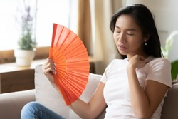 Unwell young Asian woman sit on couch wave with hand fan feel sick at home, overheated millennial Vietnamese girl relax on sofa in living room breathe fresh air from waver, suffer from heatstroke