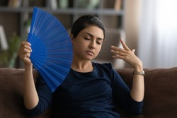 Unwell young Indian woman sit rest on sofa at home feel overheated wave with hand fan. Unhealthy tired ethnic female suffer from heatstroke use waver, struggle with hormonal imbalance. No AC concept.