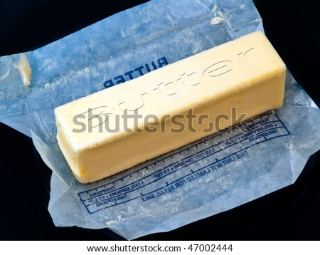Unwrapped stick of butter on a dark blue butter dish.  The word butter carved into the stick of butter was done by the photographer