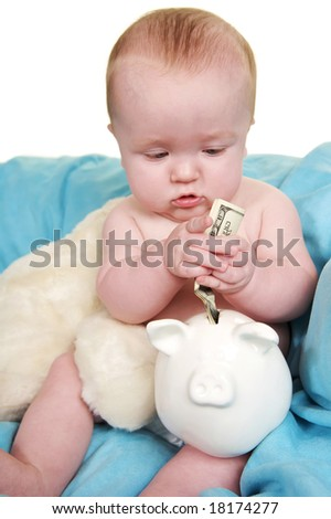 Up Close of cute baby putting money in a piggy bank