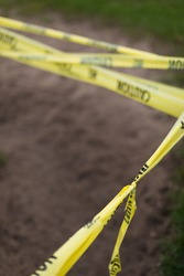 Up close photo of yellow caution tape in an outdoor setting