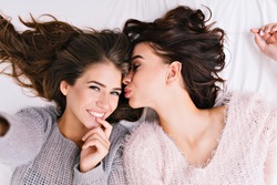 Up selfie portrait of two joyful attractive girls in woollen sweaters relaxing on bed. Chilling in the morning, having fun together, taking care, lovely moments of best  friends