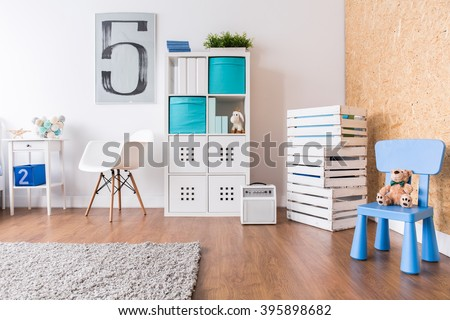 Up-to-date decor of child\'s room with wooden parquet and white furniture