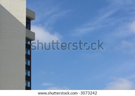 Up up and away, a commercial jet liner takes off and passes through a brilliant blue sky in front of a resort hotel - stock photo