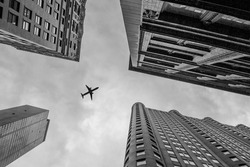 Up view with airplane in financial district, Manhattan, New York