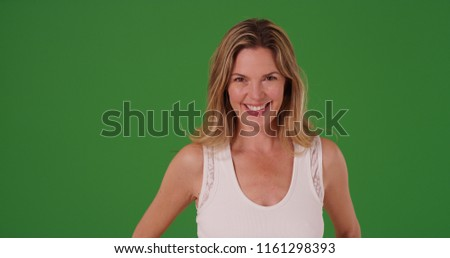 Upbeat middle aged Caucasian woman looking at camera on green screen