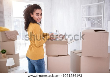 Upbeat mood. Beautiful young girl smiling at the camera while unpacking her belongings and taking a pile of books out of the box