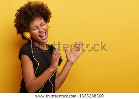 Upbeat positive African American lady enjoys deep music, closes eyes, dances with rhythm of song, holds cell phone, has perfect mood, moves actively, stands sideways over yellow studio wall.