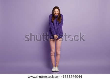 Upbeat positive lady keeps hands together, wears loose knitted purple sweater and trousers, feels happy and delighted to recieve suggestion to date, isolated over purple background. Emotions concept