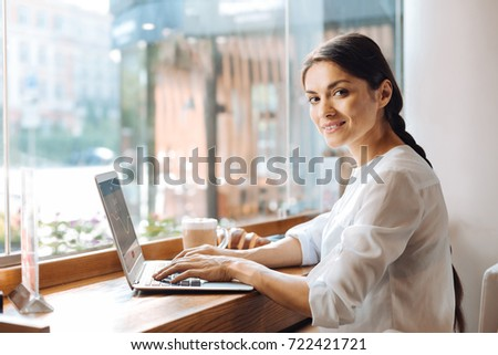 Upbeat woman typing on laptop in cafe