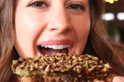 Upclose view of pretty woman smiling and eating taking a bite out of avocado toast looking into camera, horizontal shot