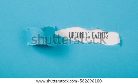 Upcoming Events message on torn blue paper revealing secret behind ripped opening.