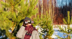 upcoming new year 2021 and christmas concept. Young woman in knitted hat and scarf looking through binoculars with numbers 2021 in eyepieces in winter forest. New year and christmas background