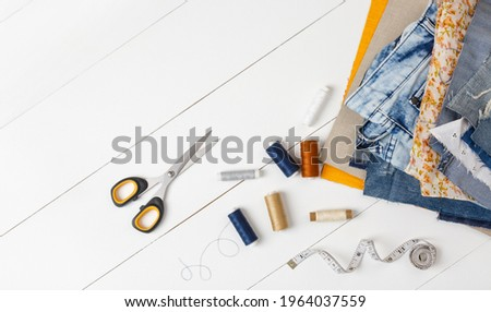 Upcycle old denim garbage. Recycling Blue jeans cut pieces, Sewing and home needlework. recycling and scissors on white background. Circular economy. Zero waste banner with copy space. DIY concept Foto stock ©