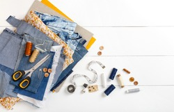 Upcycle old denim garbage. Recycling old jeans. Old blue jeans cut pieces and sewing materials ready for recycling and scissors on white background. Circular economy. Zero waste banner with copy space