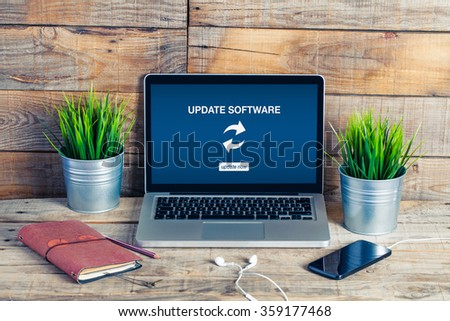 Update software notification in a laptop screen. Computer placed in a wooden work desk.