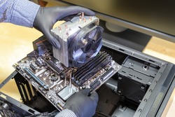 Upgrade or PC assembly concept. Technician installs a new motherboard with a large CPU cooler in a computer case