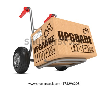 Upgrade Slogan on Cardboard Box on Hand Truck White Background