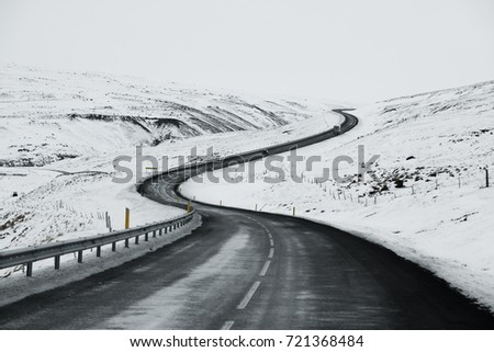 Stock Photo Uphill road landscape in winter at Iceland. Asphalt road with sideways full of snow