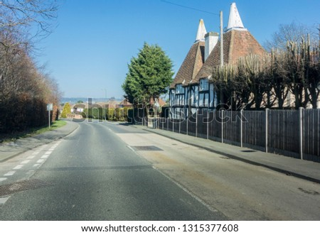 Uphill view of a country lane and ancient converted oasthouses in the village of Linton, in the county of Kent, UK