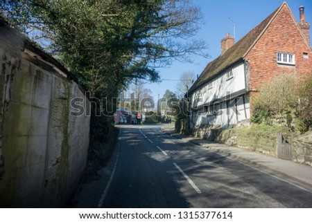 Uphill view of a country lane and ancient house in the village of Linton, in the county of Kent, UK