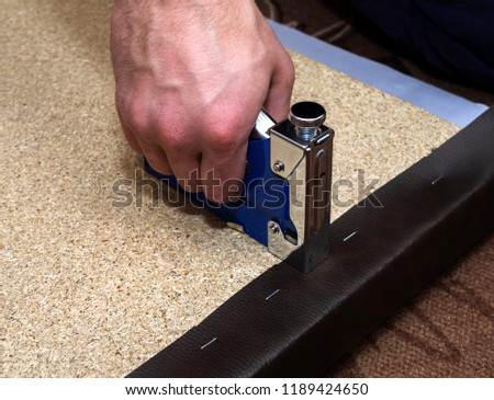Upholsterer covering particle board with brown leather using blue stapler and staples
