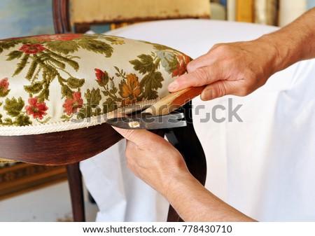 Upholsterer repairs an antique chair - Shutterstock ID 778430710