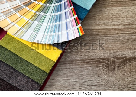 Upholstery fabric samples and color palette on table. Interior design