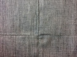 Upholstery grey fabric texture background with detail of stitching cross lines. Wrinkle fabric surface sofa seating.