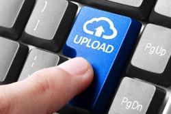 Uploading file. gesture of finger pressing upload button on a computer keyboard