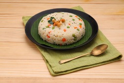 Upma made of samolina or rava upma, most famous south indian breakfast item which is beautifully arranged in a plate  and garnished with fried cashew nut and curry leaves with grey colour background.