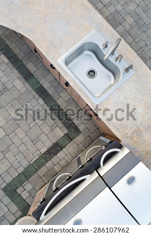 Upmarket outdoor kitchen and large built in gas barbecue in a corner design with a decorative cement counter top and sink, overhead view on a brick patio