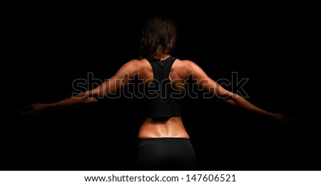 Upper body of a muscular woman from the back in a studio