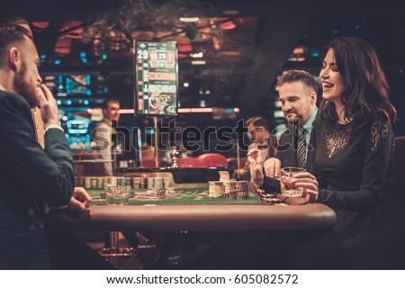 Upper class friends gambling in a casino.