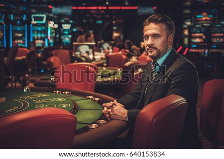 Upper class man behind gambling table in a casino