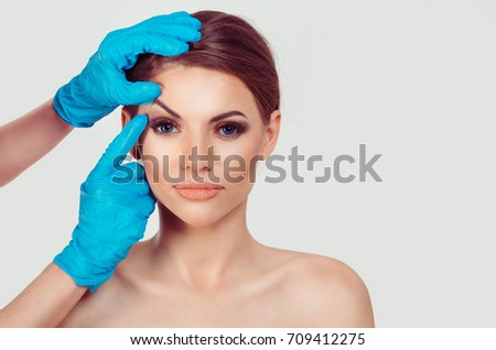 Upper eyelid blepharoplasty. Beautiful middle age woman getting ready for eyelid lift plastic surgery doctor hands in blue gloves point fingers to her eye on white. Beauty, people and health concept