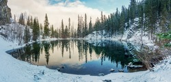 Upper Grassi Lakes in winter season. The reflection of the lake surface like a mirror. Canmore, Alberta, Canada.
