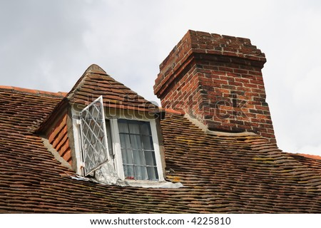 Upper level of old british house showing dormer windows and chimney