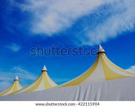 Upper part of a big colorful plastic tent. Blue sky and white clouds in background         #422115904
