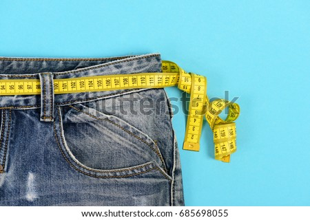 Upper part of denim trousers isolated on blue background. Blue jeans with yellow measure tape instead of belt. Close up jeans with measure tape around waist. Healthy lifestyle and dieting concept. Сток-фото ©