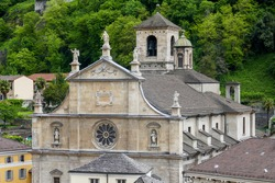 Upper part of the facade with sculpted biblical characters and roof of the 10th-century Collegiate Church of Saints Peter and Stephen in the old town of Bellinzona, canton of Ticino, Switzerland.