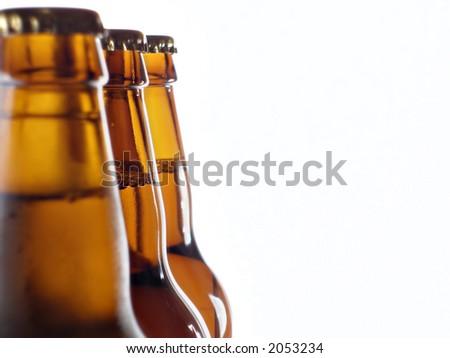 Upper part of three beer bottles