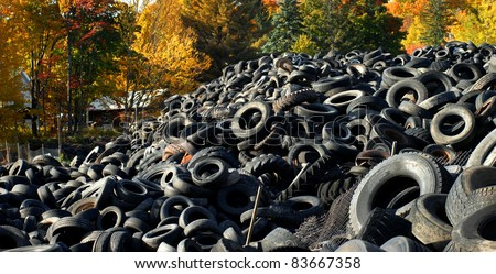Upper Peninsula, Michigan, tire graveyard is piled high.  Colorful Autumn leaves add the only beauty to the image.